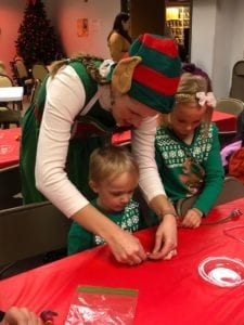 Chloe the Craft Elf helping visitors create a festive take home craft.